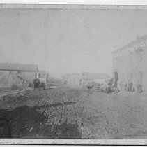 Image of Marion's Tobacco Warehouse - Marion's Tobacco Warehouse on South Main Street in Pilot Mountain. Covered wagons are on the street. Men are standing in front of the warehouse. A young girl is standing near the door on the right.