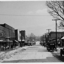 Image of West Main Street, Pilot Mountain - West Main Street, Pilot Mountain, looking east, early 1930s.  Signs for Moore's Bargain Store, Surry Drugs, and Atlantic Beer can be seen on buildings.  Several 1930s model cars are parked along the sides of the streets, a few people are walking along the sidewalks, and there is snow on the ground.