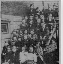 "Image of Third Grade, Rockford Street School - Newspaper clipping showing 1915-1916 Third Grade Class, Rockford Street School, Mount Airy.  Caption below the picture reads, ""50 YEARS AGO, the 1915-1916 third grade class of Rockford Street School was assembled on bleachers outside the school for a photographer to snap the photograph reproduced this week for the TIMES by Bob Watson as his latest picture in the early 1900s series."" As identified by Mr. Watson, students are,  First row: Zella Davis, May Tilley, Agnes Galloway, (unknown).  Second row, only two have been identified: Irene Beasley (first), and Myrtle Massey (third).  Third row: Katherine Moore, (unknown), Mary Council, Frank Smith.  Fourth row: (unknown), Gossie Griffith, (unknown), Guthrie Williams.  Fifth row: (unknown), Dockery Wolfe, (unknown), Nesbit Talley, Frank Hodge.  Sixth row: Jasper Wright, (unknown), Romey Poore, (unknown), Luther Wagoner."