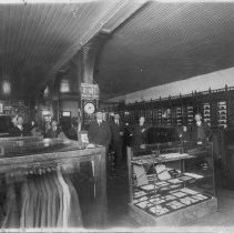 Image of Prather Clothing Store - Prather Clothing Store, Main Street, Mount Airy (where the Advance Store was later located).  Picture shows the interior of the store, with clothing, showcases, storage bins.  The men pictured are, left to right: Frank Brannock, (unknown), Jesse Franklin Prather, (unknown), (unknown), and Mr. Edwards.