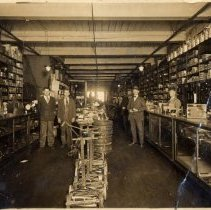 Image of Calvin Welch Store - Interior of Calvin Welch Store, South Main Street, Mount Airy, NC.  Several gentlemen are standing along the aisles, another, probably a clerk, is behind the counters.  Push lawnmowers and other yard equipment are displayed along the center aisle, and shelves and cabinets along the sides contain a variety of house and yard equipment.