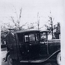 Image of Dr. Tillotson - Dr. Fount Tillotson standing beside his automobile sometime in the 1930s.  He moved to Pilot Mountain in 1926 and established his practice in an office above the old Smith DrugStore, later moving to the Blalock Building on Depot Street.  He was sometimes paid with such items as chickens and rabbits, and delivered babies for $30.  Picture from The Pilot/Centennial Section, June 28, 1989.