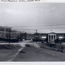 Image of Pilot Mountain School - Pilot Mountain School in the early 1940s.  The addition on the left housed the high school, and the columned building on the right housed the elementary school.  Several cars can be seen in front of the buildings.  These buildings have now been demolished.