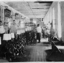 Image of Inside Mill - Picture made inside of mill in Mount Airy, thought to be Renfro, probably taken in the 1930s.  Several female employees are working  on various textile machines.  Picture was a gift to Mr. Merritt by J. Edwards of Mount Airy.