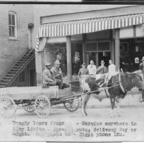 "Image of Dick Grier's Grocery and Wagon - Dick Grier Grocery Store and wagon, 109 North Bridge Street, Elkin, early 1900s.  Standing, 1) Dick Grier, 2) unknown, 3) W. D. Poplin, 4) Marvin Byrd, 5) unknown.  On wagon, 1) Duke Ward, 2) unknown.  Note at bottom of picture reads, ""Twenty Years Progress - Service anywhere in City Limits - Three minutes delivery Day or Night.  Day phone 69 - Night phone 129."""