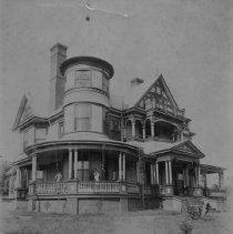 "Image of Hugh Chatham House - Elkin.  Hugh Chatham house, facing Market Street, ca. 1898.  Three adults, one holding a baby, are standing on the porch. The property was sold to the Baptist Church, and the present church stands on the site.  According to Claire Smith, this was a ""Barber House"", which was ordered from a catalog of prefab houses.  Several houses in the area were Barber houses, which were shipped in by railroad and assembled on site.  The picture was donated by Barbara Chatham."