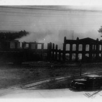Image of Old Mill Burning - Elkin.  Chatham Manufacturing Company.  The old mill burning, about 1960.  Railroad tracks and an automobile can be seen in the foreground.