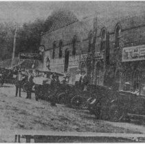 Image of Bridge Street Looking North - Elkin.  Bridge Street looking north, ca. 1915.  A number of automobiles are parked in front of the buildings, and several people are standing along the side of the street.