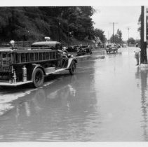 Image of Elkin. 1940 Flood - Elkin.  East Main and Standard Streets during the 1940 flood.  A fire truck is in the foreground, and some automobiles can be seen further up the road.  Several people are standing along the side of the road.