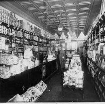 Image of Pender's Grocery Store - Elkin.  Penders Grocery Store, Market Street across from Yadkin Valley Bank, about 1915-1920.  An employee is standing behind the counter, and a customer, wearing an overcoat, is in the aisle.