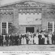"""Image of Elkin Woolen Mills - Elkin.  Elkin Woolen Mills/Chatham Manufacturing Company 1893 Mill on Railroad, south side of East Main Street, Elkin.  A large group of men and women, plus four young boys, are gathered outside the building.  Most of the men are wearing jackets and hats, all of the women have on long skirts, and the four boys also have caps.  Picture is part of a calendar titled """"Memories of Days Gone By."""""""