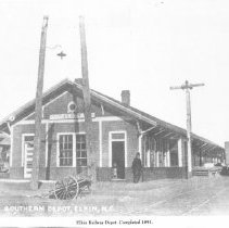 """Image of Elkin Railway Depot - Elkin.  Elkin Railway Depot, completed 1891.  A man is standing at the corner of the building , a freight car is on the tracks beside the building, and two carts can be seen at the front and side of the building.  Picture is part of a calendar titled """"Memories of Days Gone By."""""""