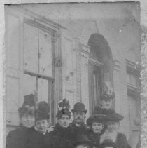 Image of Elkin Young People - Elkin.  Nine young men and women standing outside a building, probably 1880-1890.  All are wearing hats, and the women have on overcoats.  Identities are not known.