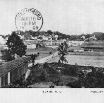 "Image of Elkin, with Covered Bridge - Elkin.  View of Elkin from across the Yadkin River in Jonesville, ca. 1905.  The old covered bridge is in the bottom left of the picture.  The picture has a Greensboro postal stamp, Aug 16 1909, and ""Publ. by Elkins News Stand"" is in the lower right hand corner."