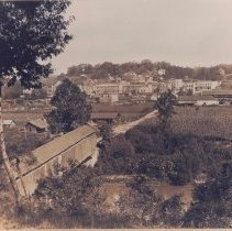 Image of View of Elkin, ca. 1907 - Elkin.  View of Elkin from across the Yadkin River in Jonesville, with the old covered bridge in the foreground, ca. 1907.  At the time it was built, with a span of 210 feet, it  was reported to be the longest wooden suspension bridge in the country.  It operated as a toll bridge with a crossing fee of five cents.