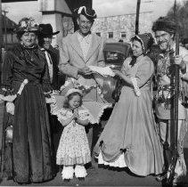 Image of Rich Atkinson and Friends - Elkin.  Richard Atkinson and friends, in costume, standing in front of the old Smithy's store on East Main Street.  Two of the men are wearing 1800s style suits, a third is dressed as a frontiersman with a long rifle.  The two ladies are wearing long dresses, one with a hoop skirt, and the little girl is wearing pantaloons and is carrying a parasol.  The occasion is not identified.