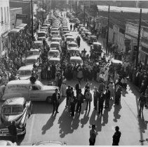 """Image of Elkin Street Celebration - Elkin.  Main Street celebration, with many people wearing costumes.  A large number of automobiles fill the street, with a """"Kluttz Music Co."""" vehicle in the foreground.  The event and date are not identified."""