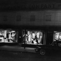 Image of Display Windows - Elkin.  Night view of display windows in the old J. C. Penny Company store on East Main Street.  Women's clothing and home gifts are featured.  An automobile can be seen in the right hand corner of the picture