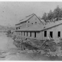 Image of Elkin Valley Woolen Mill - Elkin.  R. R. Gwyn & Company's Elkin Valley Grist Mill being enlarged to house Elkin Valley Woolen Mill, 1877.  Several men are working on the roof.  Two women are standing on the bank of the creek, and a rowboat is pulled up to the bank.  The dam can be seen in the background on the left.