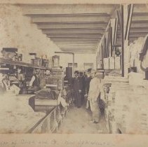 Image of Interior of Click & Co. - Elkin.  Interior of the Click and Company store, Main Street, Elkin, ca. 1895.  The building  later became Spainhour's, and is now occupied by a bank.  The counters are stacked with dry goods, and several men are standing along the aisles and behind the counter.  Identifications, as supplied on the back of the picture, are:  Left to right: Walter Worth or E. G. Click, Lythe Hunt, A. G. Click, R. L. Hubbard, J. S. Roth, two workers unknown - Harry Sprinkle?  Salesmen: Lytle Hickerson Hunt, Madison Eugene Motsinger, Walter H. Worth.  From the Elizabeth Hubbard Harris collection.