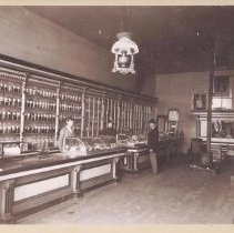 """Image of Dr. Ring's Drug Store - Elkin.  Interior of Dr. Ring's Drug Store, Elkin, ca. 1897.  Two employees are behind the counter and a customer wearing a jacket and hat is standing in front.   Notes on the back read: """"about 1897.  This store burned 1898.  Dr. Ring's drug store, believe John Roth."""" Additional information, not verified, says that the first delivery was made by a boy on a bicycle, Elkin's first parcel post business.  From the Elizabeth Hubbard Harris collection."""