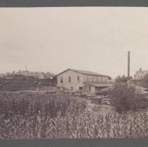 """Image of Elkin Veneer Factory - Elkin.  Elkin Veneer Factory, ca. 1898.  Information on the back of the picture reads: """"Located, at the time this picture was made, on the lot between the present Charles Neaves home (which was the John S. Roth home), and the present Raymond Harris home (which was the R. L. Hubbard home) on Surry Ave., Elkin, N. C.""""  Several men can be seen at work in the yard beside the building.  From the Elizabeth Harris collection."""