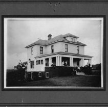 """Image of Hines House - Home of Madison """"Matt"""" Hines and Stella Parker Hines, North Main Street, Mount Airy, built ca. 1920.  Several people, including Mr. and Mrs. Hines and their children,  can be seen standing and sitting on the front porch."""