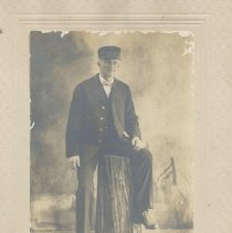 """Image of George McGee - Picture of gentleman posing at a tree stump.  He is wearing a hat that says """"Conductor""""  and on the collar is """"C.M. & P.S.""""  A penciled note identifies him as George McGee."""
