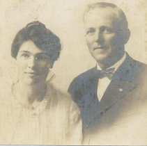 Image of Mr. & Mrs. George McGee - Picture of Mr. and Mrs. George McGee, prossibly around 1918.  She is wearing a tucked blouse and a small necklace, he has on a suit with bow tie.