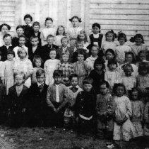 Image of Pilot Mountain School Students - Photocopy of Pilot Mountain School students in 1912.  The children are posed outside the school building, with those on the front row kneeling, students on back rows probably standing on benches.  Several of the boys are wearing jackets and ties, and several of the girls are wearing longwaisted dresses. Among those pictured are (?) Douglas, Eugene, Nelson; (?) Iddings, Clayton Fulk, Brian Badgett, Ralph Fulk, Clonnie Bell Lewis, Erma Barnes, Wilma Snow; Raymond Lewis, Claude Swanson, Quentin Carson, Paul Ashburn, Blake Carson, Ona Mae Boles  Picture submitted by Ada Badgett.