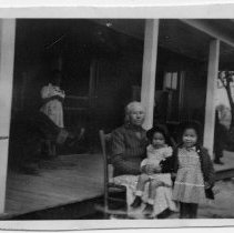 Image of Tucker Family Members - Ollie Grogan Tucker is sitting in the front yard of her home. Sitting on her lap is great granddaughter, Betty Lou Hickman. Standing by her chair is great granddaughter Anna Mae Hickman.  The boy on the porch with wooden horse is her grandson, Samuel Howard Tucker. The year is 1944.
