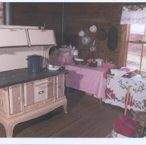 Image of Tucker Homeplace - Tucker Homeplace Interior: view of the kitchen. The stove is similiar to the one Ollie Tucker owned. It is a wood burning stove with six burners, a water tank on the side and warming closets at the top. Pots and pans are hung on the wall in the same spots where Ollie hung her pots. The vintage Christmas cloth belonged to Charlie and Ollie's daughter-in-law, Rosa Green Tucker. Picture taken by Robert Merritt in December 2006.