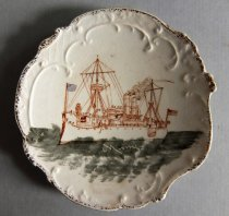 Image of Plate. 6.5 x 6.875 inches. Smaller plate of the same set as 95.01.112. Features same picture of the Maine but smaller - Plate, Decorative