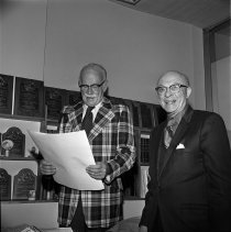Image of Robert Hutton and Les Storrs Studying a Document - 1975/02/20