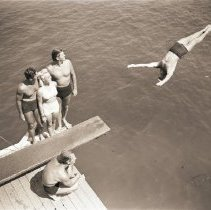 Image of Johnny Weissmuller Observes Diver at Manoa Paddleboard Club, 1944 - 1944/07/01
