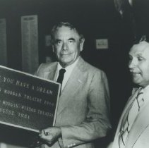 Image of Glenn Ford Holding Morgan-Wixson Theatre Plaque - late 1900s