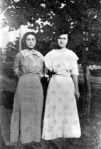 Image of Two women, one in medium-colored dress.