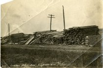 Digital scan of a sepia-toned photo taken of stacks of lumber piled in Windsor for the construction of the Michigan Central Railway Tunnel between Detroit and Windsor below the Detroit River