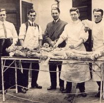 Image of Five men with one cadaver, outside.