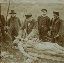 Image of Four men with cadaver, outside.