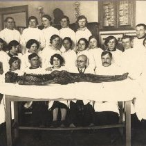 Image of Group with a cadaver. Two infant skeletons in background.