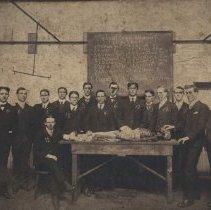 Image of Fourteen men with a cadaver.