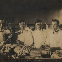 Image of Four men with a cadaver and a skeleton.