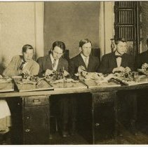 Image of Five men and one woman sitting at desks dissecting cats (dogs?). Printed on postcard paper. On back: Nels Otterstad, St. Alax College, June 1, 1909.