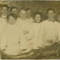 Image of Group of men and women standing behind dissected cadaver. Printed on postcard paper.