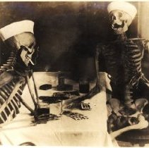 Image of Two skeletons posed as though playing cards, wearing sailor hats, smoking and drinking.