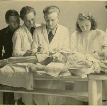 Image of Four men and one woman dissecting a cadaver.
