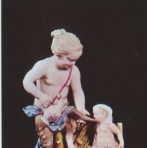 Image of Faun feeding infant faun by means of a cows horn -