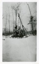 Image of Men setting log on top of trailer
