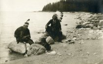 Image of Indians sitting on rocks on beach with dog
